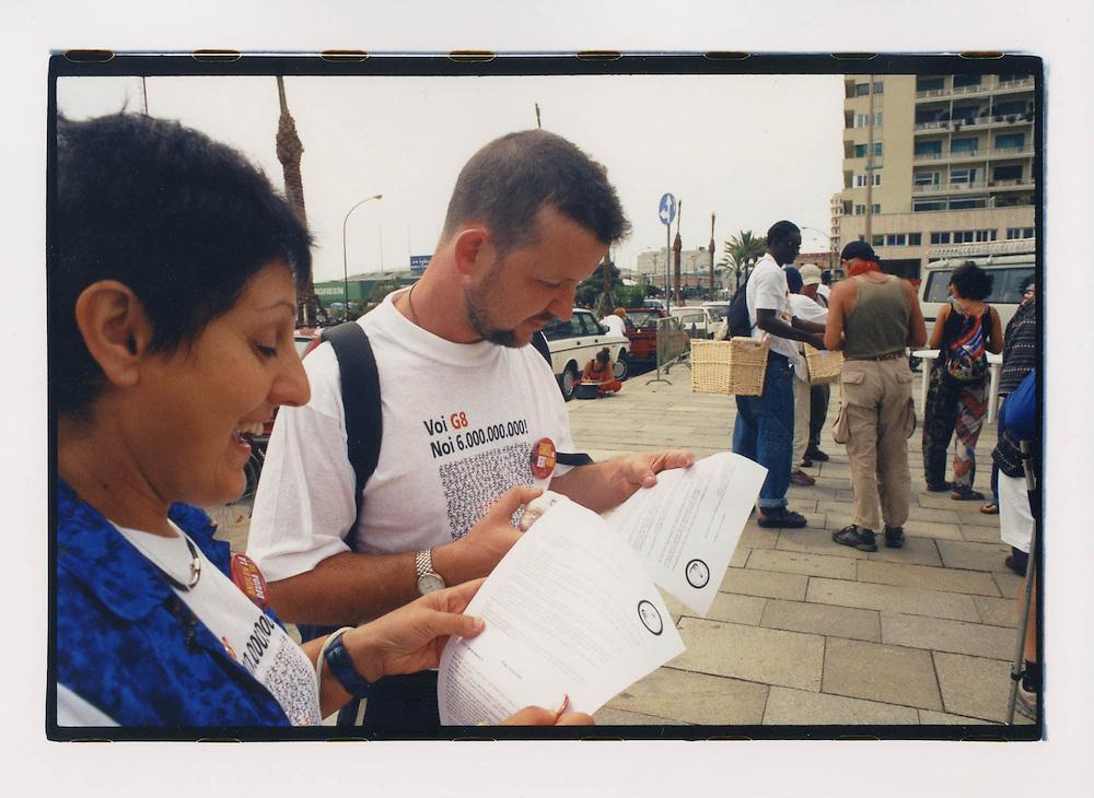 """Proteste contro il summit del G8, Genova luglio 2001. Piazzale Rossetti, 19 luglio. Manifestanti distribuiscono aglio, in una azione chiamata """"Garlic for Peace"""", Aglio per la Pace. Poco tempo prima del G8 di Genova, il premier italiano Silvio Berlusconi aveva dichiarato alla stampa di odiare l'aglio, e che lo avrebbe bandito dai menu ufficiali del summit."""