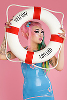 Young woman holding float tube over pink background