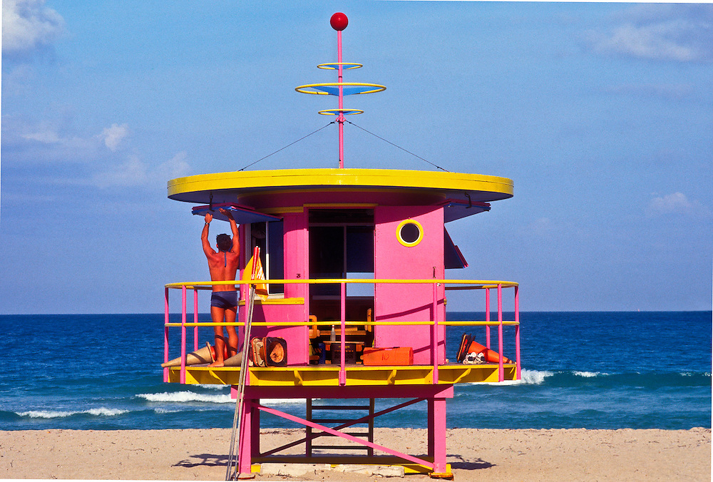 A fit-looking Miami Beach lifeguard stands on a Post-Modern lifeguard station designed by architect William Lane and pop artist Kenny Scharf. <br />