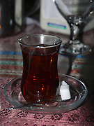 A glass of strong Turkish tea with lumps of sugar