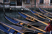 A row of gondolas at rest in canal, Venice, Italy..Subject photograph(s) are copyright Edward McCain. All rights are reserved except those specifically granted by Edward McCain in writing prior to publication...McCain Photography.211 S 4th Avenue.Tucson, AZ 85701-2103.(520) 623-1998.mobile: (520) 990-0999.fax: (520) 623-1190.http://www.mccainphoto.com.edward@mccainphoto.com.