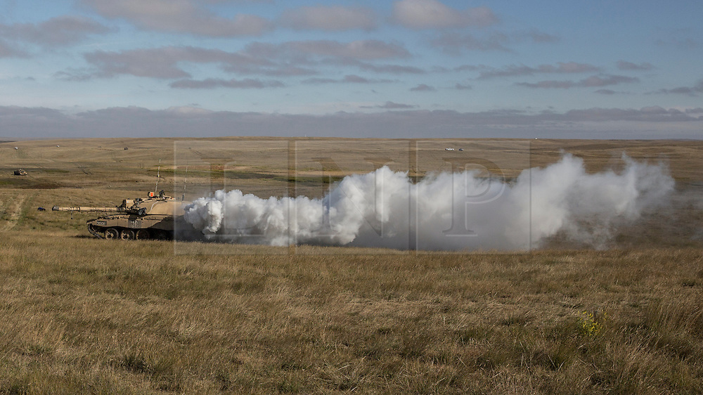 © Licensed to London News Pictures. 08/10/2014.  British Army Training Unit Suffield (BATUS), Canada. A Challenger 2 main battle tank releases diesel onto it's exhaust to create a smoke shield that will be used to assist the infantry as they invade one of the enemy villages in a training exercise which prepares the troops for war. <br /> <br /> BATUS has been home to the Army for the past 42 years .  It is the only place where all elements of the British Army train together for war.  The soldiers are put to test on everything from armoured vehicles to infantry tactics.        Photo credit : Alison Baskerville/LNP