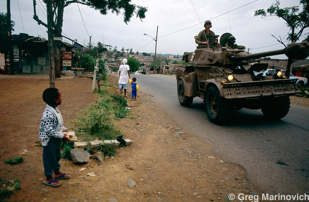 KwaMashu township, KwaZulu Natal, South Africa, 1995: SADF armoured vehicles patrol the volatile KwaMashu township in 1995 as a young boy look on.