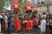 Men spinning tall headdresses with paper flowers in the parade celebrating the festival of Ganesh Chaturthi, marking the birth of the Hindu god Ganesha, on the streets of the La Chapelle area of the 18th arrondissement of Paris, France, on Sunday 1st September 2019. The annual religious festivities and parade take place near the Ganesha Temple of Paris, or Sri Manicka Vinayakar Alayam Temple, the largest Hindu temple in France. Ganesha is the elephant-headed Hindu God of Beginnings, son of Shiva and Parvati, who represents love and knowledge. Picture by Manuel Cohen