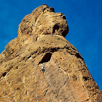 A natural rock formation at Smith Rock state park in eastern Oregon that resembles a face looking up into the sky, with a rock climber.