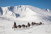Tsaatan reindeer herders traverse open ground towards a high pass, Hunkher mountains, northern Mongolia