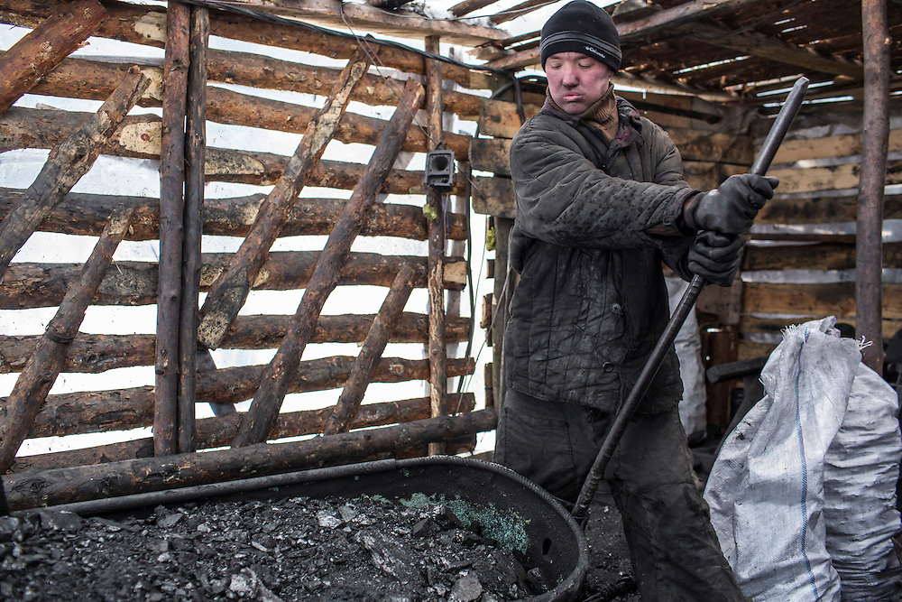 SNEZHNE, UKRAINE - JANUARY 25, 2015: Dmitry Kontratenko unloads a tub full of coal at the small private coal mine where he works in Snezhne, Ukraine. The mine produces approximately 15 tons of coal per day with a crew of four men. CREDIT: Brendan Hoffman for The New York Times