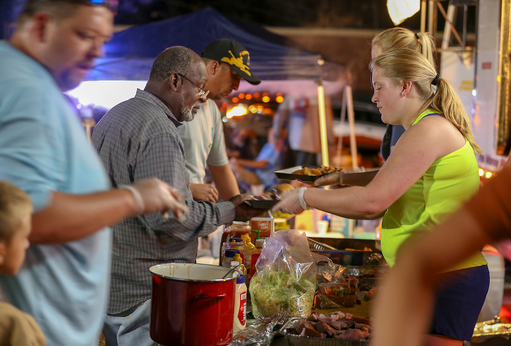Allen McCullough, 66, of Blountstown, Florida takes a plate of food from Bryanna Hope, 18, Friday, Oct. 12, 2018 in Blountstown. Before Hurricane Michael made landfall Kyle Dalton decided to drive his truck stocked with two smokers and plenty of meat to the town he grew up in. Dalton said he has fed over 2,000 people yesterday and well over that today.