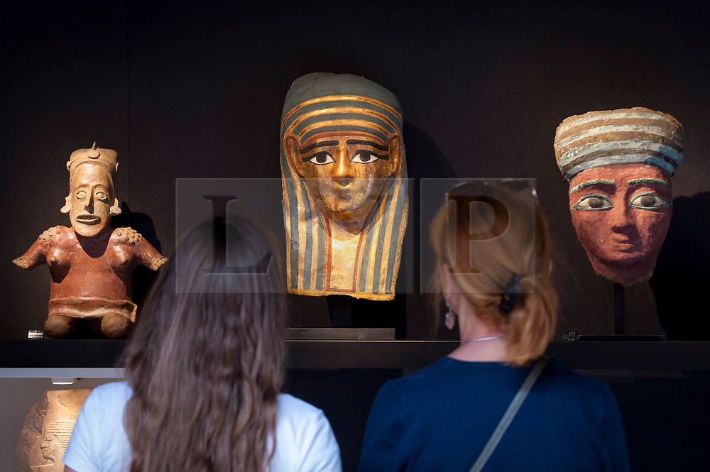 © Licensed to London News Pictures. 20/06/2018. LONDON, UK. Visitors view ancient artifacts from Mexico (L), Egypt (C & R), all between 2,000 and 2,500 years old at The Art & Antiques Fair Olympia which runs 20 to 27 June at Kensington Olympia.  Photo credit: Stephen Chung/LNP
