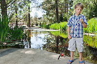 Boy adjusting fishing rod's line while standing by lake