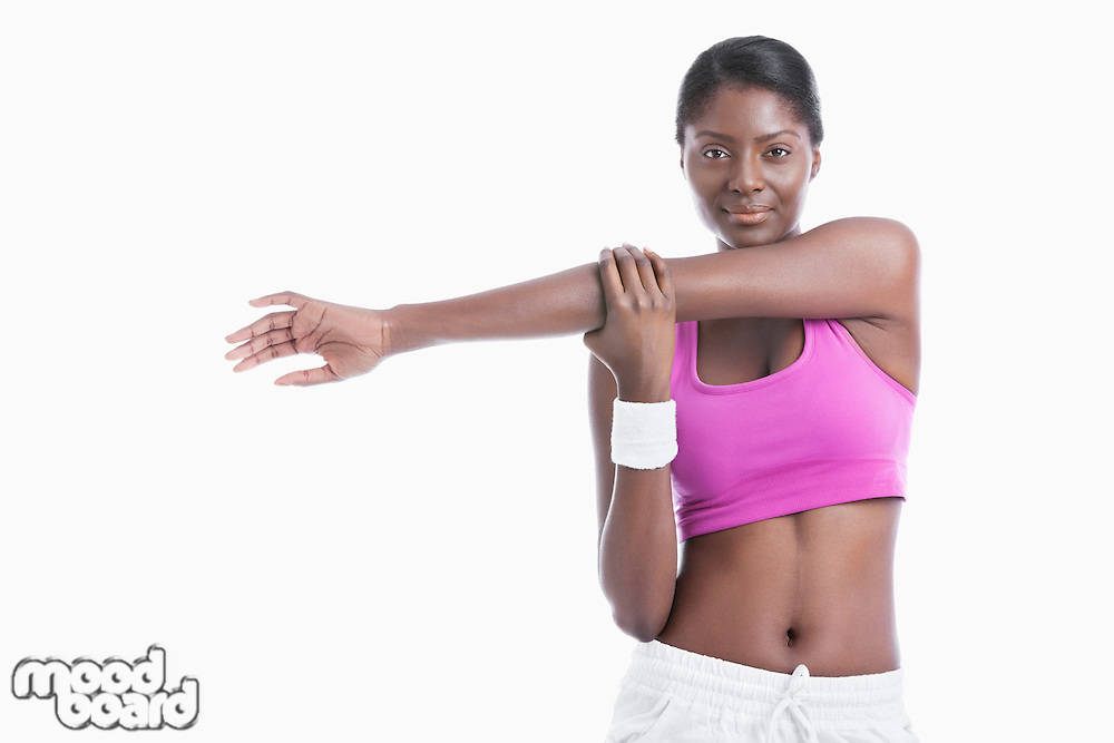 Portrait of an African American young woman stretching arm over white background
