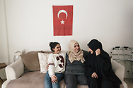 Vahide Şefkatlıoğlu, (centre) at her sister's home with her two daughters, Aisha (right) and Zainab (left) in Esenler, Istanbul, Turkey. Vahide's husband was killed by a military tank that injured her and left her an amputee.