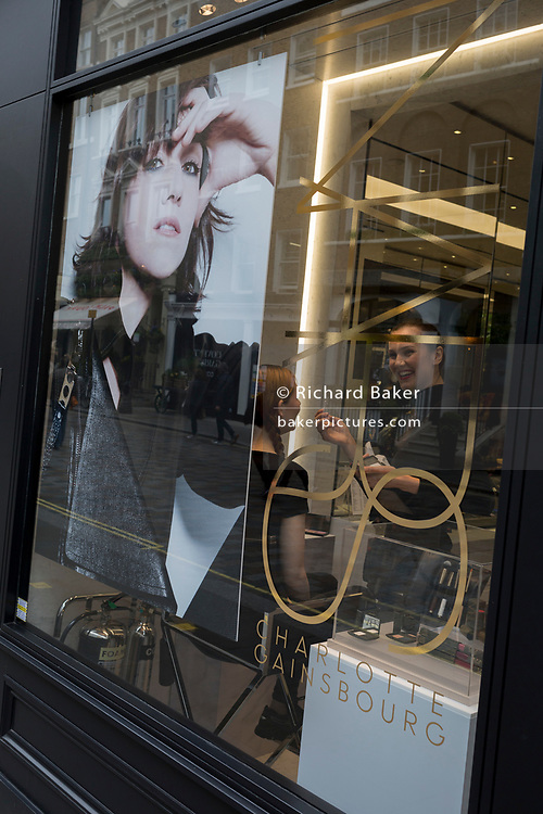 A make-up artist smiles while applying a makeover to a customer in the window of a Covent Garden hairdressers, on 4th May 2017, in London, England.