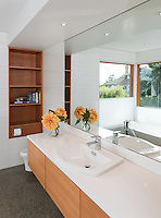 The master bathroom in this new contemporary build features a poured aggregate cement floor with Vancouver Island rock, douglas fir trim and a big soaker tub surrounded by windows that look to the sky and ocean beyond.