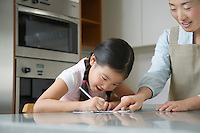 Mother standing at kitchen counter Pointing at Daughter's Drawing