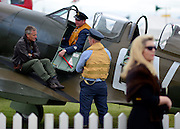 © Licensed to London News Pictures. 16/09/2012. Goodwood, UK . Spitfire pilots take a break on the wings of their aircraft. People enjoy the atmosphere at the 2012 Goodwood Revival. The event recreates the glorious days of motor racing and speed, participants are encouraged to dress in period dress. Photo credit : Stephen Simpson/LNP