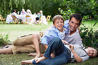 Father and two sons (7-10) having fun on grass in garden