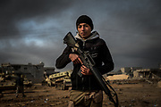 An Iraqi soldier poses for a photo in the town of Gayyara, south of Mosul, on December 7, 2016. Before the town was liberated by Iraqi forces in August 2016, IS militants set fire to several oil wells. Thick, toxic smoke continues to shroud the city and surrounding areas.