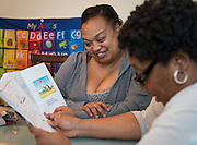 Monica Bass, left, goes over curriculum with Home Instruction for Parents of Pre-K Youth (HIPPY) instructor Nadine Hypolite, right, at her home, March 11, 2014.