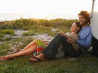 Couple leaning against van wheel van parked on cliff above ocean