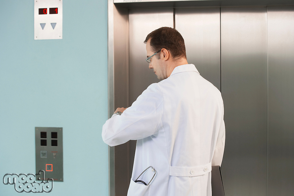 Physician Checking His Watch by elevator