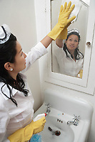 Young housemaid cleaning mirror above wash basin