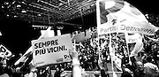 """Some Partito Democratico's supporters - the Italian left-wing Party - hold flags and a banner that reads """"Closer and closer"""" before the beginning of Matteo Renzi's speech during a political campaign convention for the Italian government elections in Turin, April 12, 2014."""