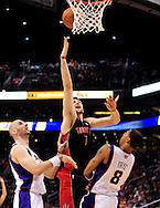 Mar. 23, 2011; Phoenix, AZ, USA; Toronto Raptors center Andrea Bargnani (7) puts up a basket against the Phoenix Suns center Marcin Gortat (4) and teammate forward Channing Frye (8) at the US Airways Center. Mandatory Credit: Jennifer Stewart-US PRESSWIRE