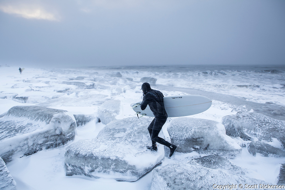 Gart Curtis runs back up the beach over big chunks of ice in a snow blizzard while surfing Ninilchik, Alaska in winter.