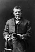 Booker T. Washington (1856-1915) African American educator and  Civil Rights leader. Photographic portrait of Booker seated and holding a open book.