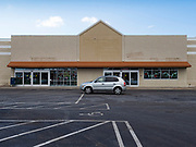 """26 FEBRUARY 2020 - FARMINGTON, MINNESOTA: A motorist drives past the closed Family Fresh Market grocery store Farmington, MN, about 30 minutes south of the Twin Cities. Farmington, with a population of 21,000, is a farming community that has become a Twin Cities suburb, the population has doubled since the 2000 census. The Family Fresh Market, Farmington's only grocery store, closed in December, 2019. The closing turned the town into a """"food desert."""" The USDA defines food deserts as having at least 33% or 500 people of a census tract's population in an urban area living 1 mile from a large grocery store or supermarket. Grocery chains Hy-Vee and Aldi both own land in Farmington but they have not said when they plan to build or open stores in the town.     PHOTO BY JACK KURTZ"""