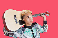 Teenage boy carrying guitar over his shoulder over pink background