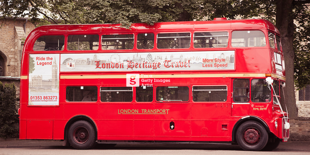A red double decker bus dressed to ferry wedding guests around.