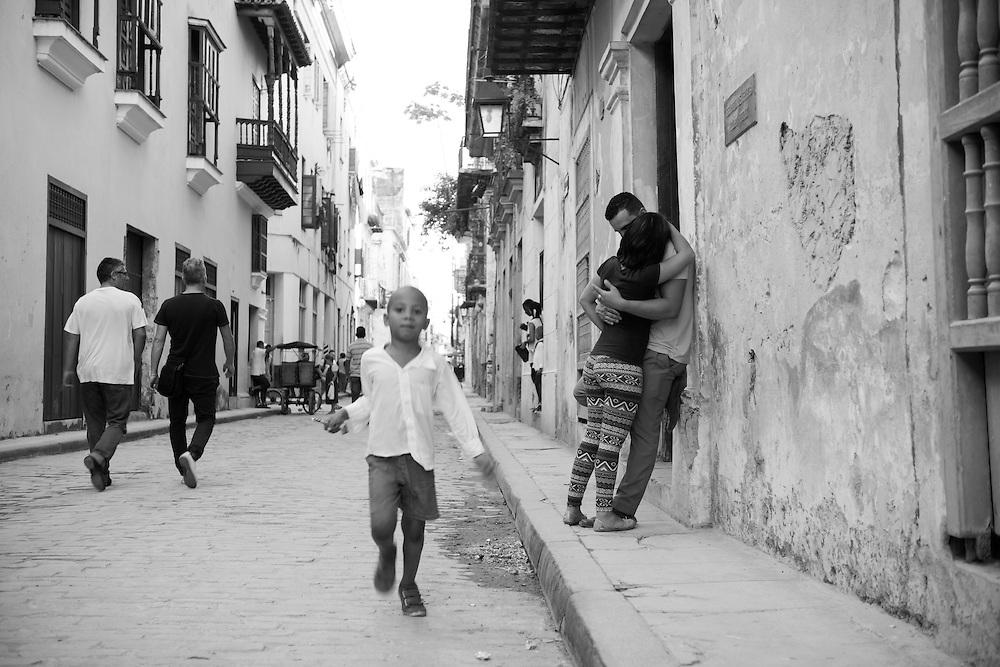 A young boy runs toward a photographer as a couple embraces nearby in Habana Vieja (Havana, Cuba - December 4, 2014)