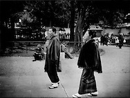 Kimono clad Tokyoites completely unaware of homeless men they pass during the Coming of Age holiday celebration at Senso-ji Temple, Asakusa, Tokyo, Japan.