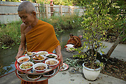 On their return, monks from the temple help carry in the trays of food offered. Monks on boats travel small klongs or canals collecting alms in the early morning.