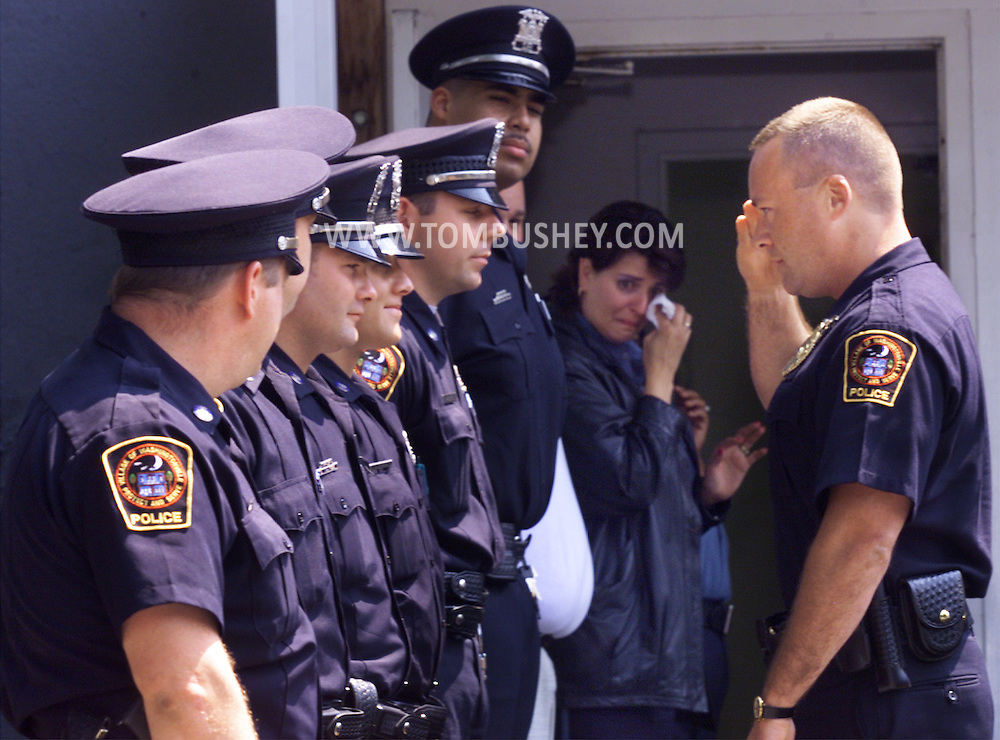 TOM BUSHEY/The Record.Washingtonville Police Chief Nick Kuzmiak, left, salutes a member of the department as dispatcher Maria Fleming, rear, wipes her eyes during a ceremony  marking Kuzmiak's final day at the department. Kuzmiak, 39, retired yesterday after 12 years as police chief..(June 27, 2001).