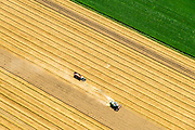 Nederland, Groningen, Stadspolder, 05-08-2014;  graanoogst in het Oldambt. De combine maait het graan en dorst dit direct, het zgn. maaidorsen. Naast de maaidorser een kipwagen voor de afvoer van het graan. De Stadspolder is een zeekleipolder gelegen aan de Dollard Noordoost-Groningen.<br /> Grain harvest in the Oldambt. The combine reaps the grain and threases it. Next to the combine harvester a dumper for the discharge of the grain.<br /> The polder consists of sea clay and is situated in to the  Northeast of Groningen.<br /> luchtfoto (toeslag op standard tarieven);<br /> aerial photo (additional fee required);<br /> copyright foto/photo Siebe Swart