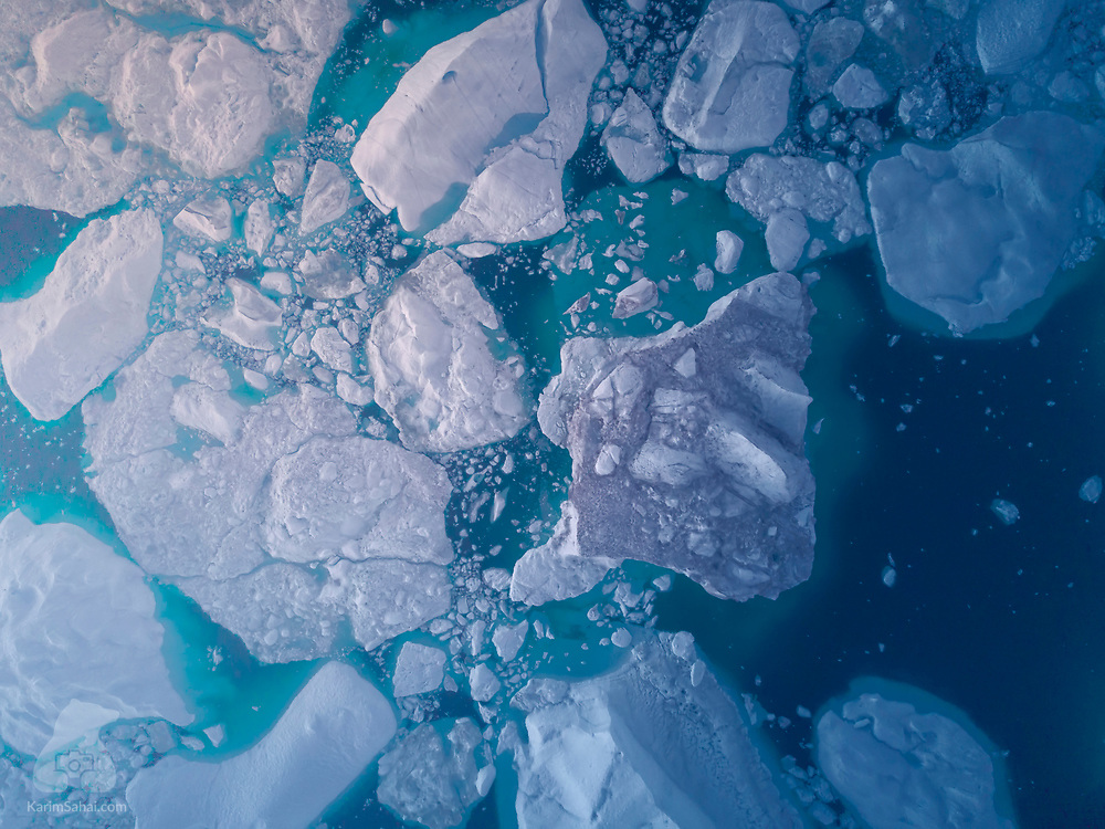Icebergs and fragments of ice float away from the Sermeq Kujalleq glacier, the fastest moving glacier in the world located near Ilulissat, Greenland