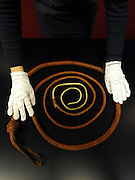 © Licensed to London News Pictures. 08/12/2011, London, UK. A Bonhams employee holds a a bullwhip used by Harrison Ford as Indinana Jones in the film series of the same name. The prop is expected to fetch 30,000-35,000 GBP.  Bonhams, London, photocall for entertainment memorabilia today, 8th December 2011. The auction takes place on Thursday 15th December. Photo credit : Stephen Simpson/LNP