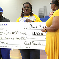 Chiquita Bobo, an assistant teacher with special needs at Milam, presents Teetta Vasser with a $50,000 check to help her son, Keshun, 12, who was shot in the neck in September that paralyzed him from the waist down. The money will go towards a wheelchair accessible van and other items to help with Keshun's daily needs. Fundraisers through the schools and his church made the donation possible.
