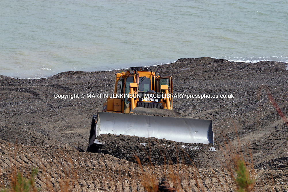 Protecting the sea wall from storms by piling shingle on the beach, Folkstone.