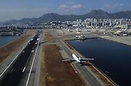 Hong Kong. planes landing on THE OLD Kai Tak airport in the CENTER OF THE city. THE AIRFIELD IS BUILD ON A RECLAIMED LAND          / avion  atterissant au dessus de la mer et la ville, sur l'aéroport de Kai Tak, . La piste d'attérissage est construite sur un polder, juste devant  Mongkok, le quartier le plus dense de la planète       premier Airbus A 340 livrés a Cathay pacific  / R82/    L1086  /  R00082  /  p0006040