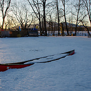 A canoe sits in the snow waiting for the warm days of summer.