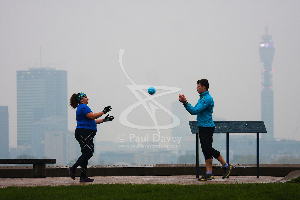 Primrose Hill, London, October 30th. As mist shrouds London's skline, fitness fanatics run and work out on Primrose Hill. Pictured: A personal trainer and his client work out on Primrose Hill.