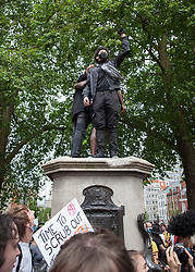 **Previously unseen pictures**<br /> © Licensed to London News Pictures; 07/06/2020; Bristol, UK. Protesters climb on to the empty pedestal where a statue of Edward Colston was pulled down with a rope during a Black Lives Matter march through the city centre. The death of George Floyd, who died after being restrained by a police officer In Minneapolis, Minnesota, caused rioting and looting across the U.S.A and protests across the world. Photo credit: Mark Simmons/LNP.