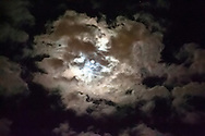 Moon behind storm clouds.
