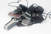 A pile of old disused mobile phones and chargers