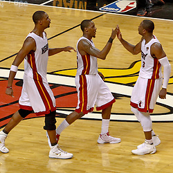 Jun 19, 2012; Miami, FL, USA; Miami Heat point guard Mario Chalmers (15) and power forward Chris Bosh (1) and shooting guard Dwyane Wade (3) celebrate at mid-court during the fourth quarter in game four in the 2012 NBA Finals against the Oklahoma City Thunder at the American Airlines Arena. Miami won 104-98. Mandatory Credit: Derick E. Hingle-US PRESSWIRE