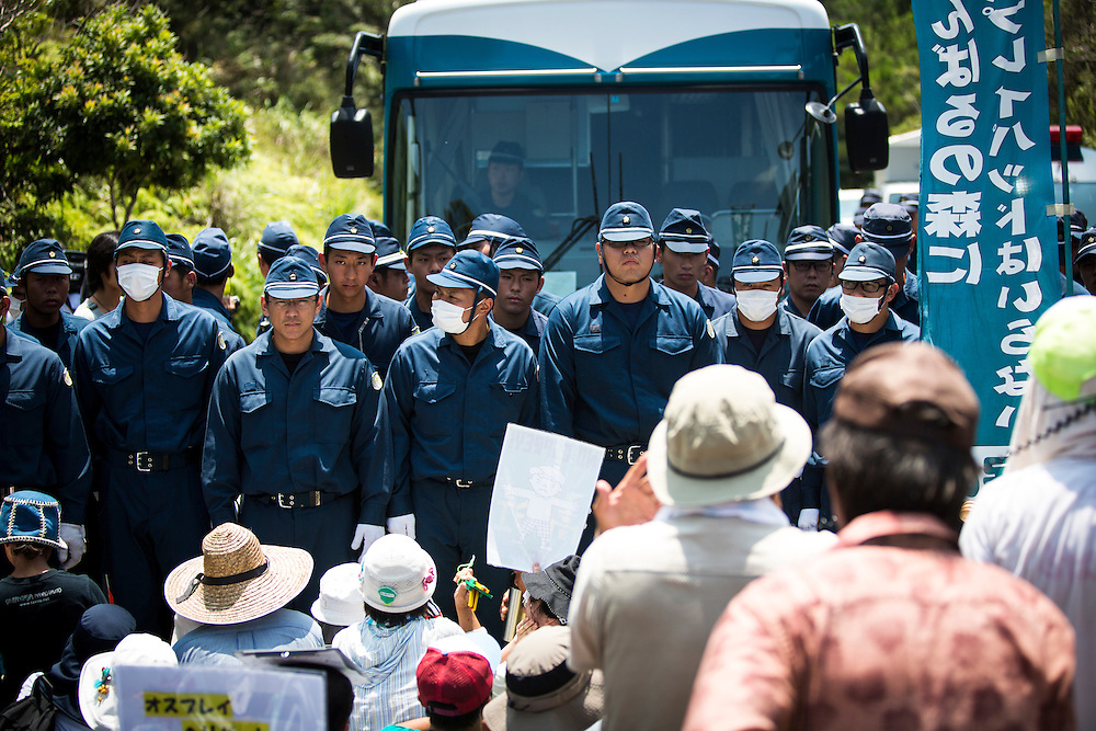 OKINAWA, JAPAN - AUGUST 19 : Police is seen to guard the construction trucks from Anti U.S base protesters as they staged a sit-in protest against the construction of helipads in front of the gate of U.S. military's Northern Training Area in the village of Higashi, Okinawa Prefecture, on August 19, 2016. Japanese government resume construction of total six helipads in a fragile ten million year old Yanbaru forest that is home to endemic endangered species such as the Okinawan rail and Okinawan wood pecker. (Photo by Richard Atrero de Guzman/NURPhoto)
